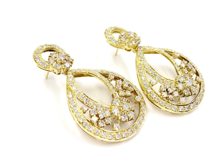 These romantic 18 karat yellow gold and round brilliant diamond drop earrings are the perfect combination of contemporary design with a hint of Art Nouveau influence. 10.85 carats of beautiful diamonds adorn this show stopping pair with quality of