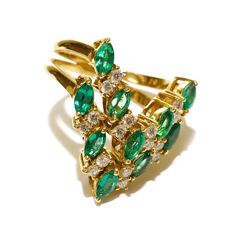 18 Karat Yellow Gold Marquise-cut Emerald Double Diamond Ring. A double row ten prong-set marquise emeralds and sixteen round diamonds in a v-shape. The double band is open on the sides and meet at the back. Ring size is 7. The Emeralds measure 4mm