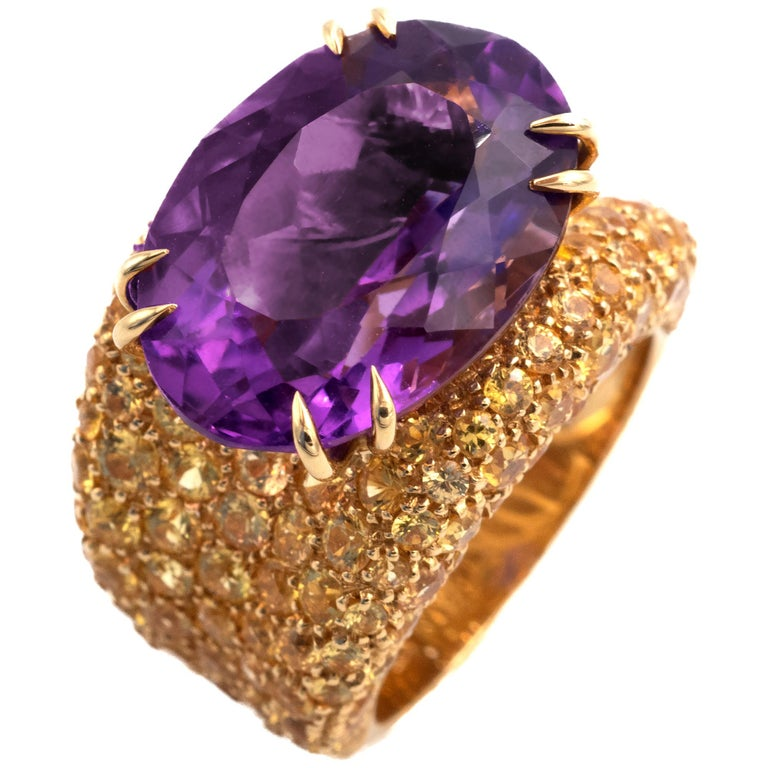 Stunning 18 karat cocktail ring, a lively amethyst is set across the finger, underneath the ring soft curves are carpeted with sparkling round brilliant cut yellow sapphires. The make is excellent with a nice hefty feel.  Yellow sapphires: 5,13