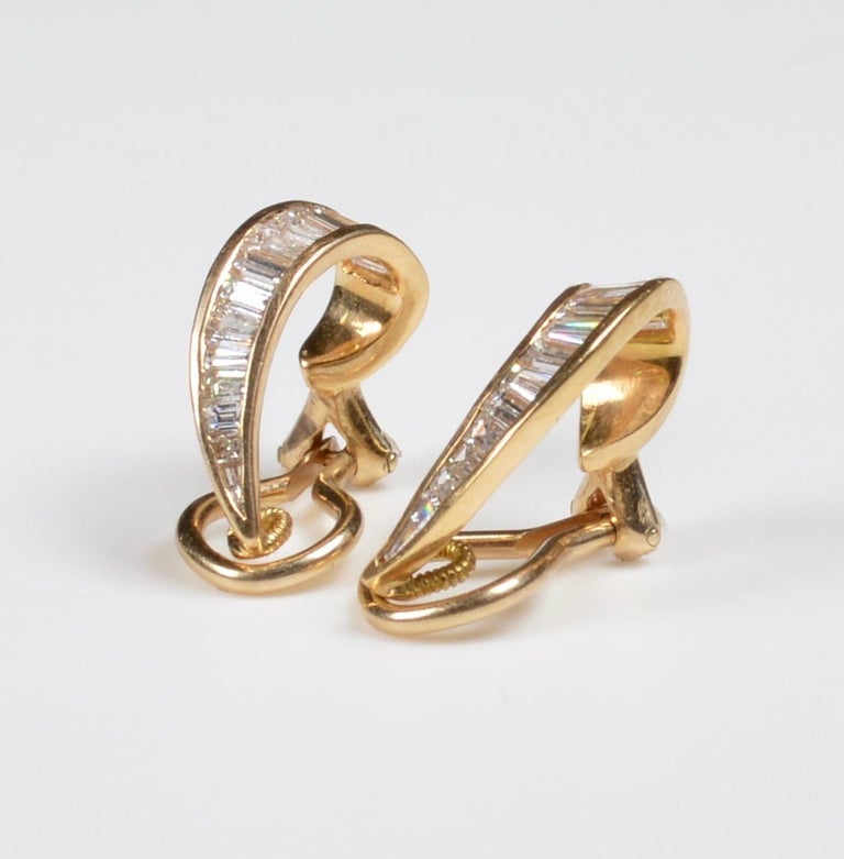 18kt Gold and Diamond Earclips, each a curving line of channel-set diamond baguettes, lg. 5/8 in.