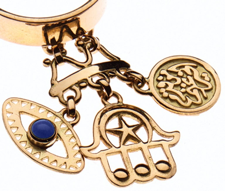 An 18 Karat Gold ring decorated with iconic 'Eye' and 'Hand of Fatima' cultural charms and calligraphy engravings: