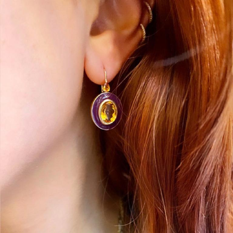 A pop of plum enamel sets off the warm color of this golden citrine center stone.  The oval setting is topped with pear shaped yellow sapphires.  An unusual color palette, this design updates a classic to a high fashion level. Materials: 18 Karat
