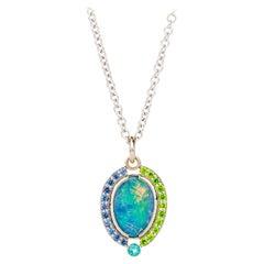 18 Karat Gold Australian Black Opal Necklace with a Sapphire and Garnet Halo