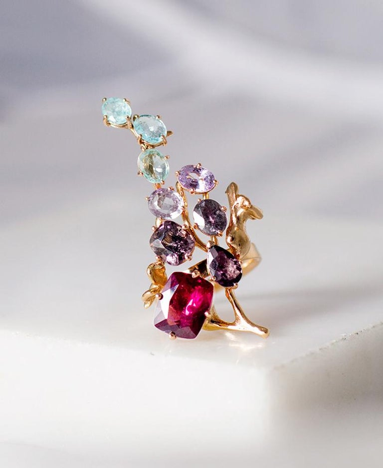 This 18 karat rose gold contemporary cluster brooch by artist is encrusted with: fancy pink and green sapphires, Paraiba tourmalines, spinel, 14.36 carats in total.   The work is accurate and the piece sparkles as the perfect highlight. This ring