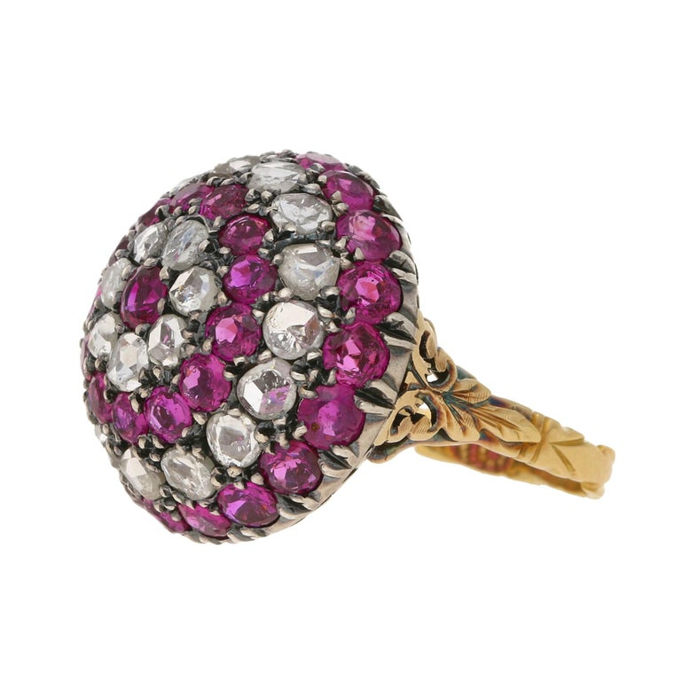A Late Georgian style bombe cocktail ring claw set with thirty three Burmese rubies and twenty two rose-cut diamonds set in silver on gold. The underside of the ring is adorned with an ornate pierced openwork undercarriage leading to a gold carved