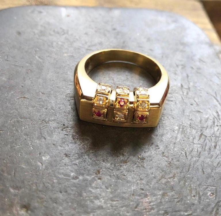 18k Code Ring features a thick solid 18k Yellow Gold band with a three row moveable dial, featuring white diamonds and three rubies.  18k Yellow Gold, White Diamonds, Rubies  From the James Banks Code Collection