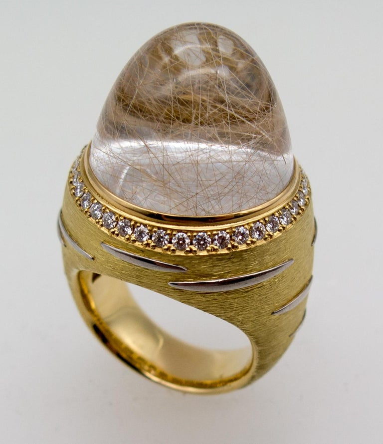An eye catching and unusual dinner ring featuring a huge dome of rutilated quartz.   it looks like threads floating through vodka or gin, and in fact, it's threads of rutile needle inclusions floating in a suspension of crystal created underground