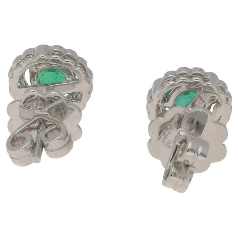 A pair of elegant emerald and diamond earrings in the classic cluster design. Set in 18ct white gold. Total emerald weight 0.98ct, total diamond weight 0.28ct, with a secure post and butterfly fitting.