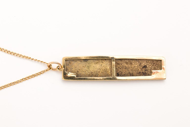 Circa mid-20th century Modern style hand made 18 karat ebonized gold necklace that features a linear U-shaped pendant. It has been ebonized in a warm brown and comes with an 18 karat gold chain. The chain and pendant measures 26.00 Inches long.