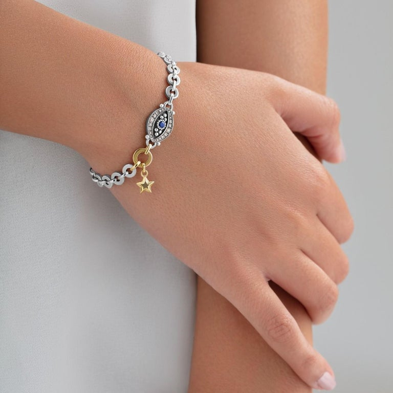 18 Karat Gold and Sterling Silver Eye & Star Bracelet, set with precious stones.   Featuring a suspended gold star, this 18 Karat Gold and Sterling Silver bracelet carries an eye set with 0.33 carat Champagne Diamonds and 0.20 carat