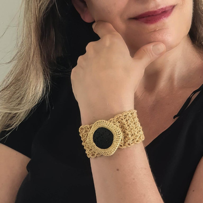 Beautifully crafted hand crochet gold thread bracelet (19.82 grams gold) with a natural black Lava stone (weighing 13.6 grams/68 carats). The combination of the elegant intricate gold stitches with the Semi Rough Lava Stone is very