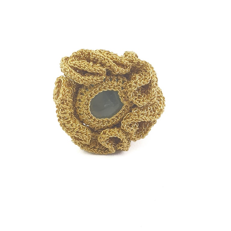 A beautifully crafted, crochet ring. Handmade with 18 Karat gold thread (13.25 grams) and a milky light blue Aquamarine (weighing 1.75 grams/8.75 carats). This ring is a US size 7. It can be stretched a little to fit larger sizes.  Shenhav's