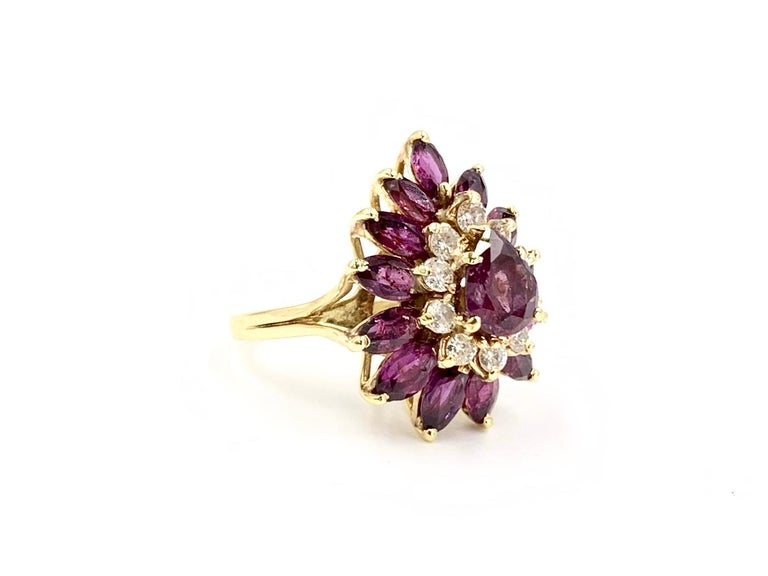Circa 1975, this 18 karat yellow gold dramatic cocktail ring features Merlot colored fancy cut rubies and white round brilliant diamonds. Center pear shape ruby weighs approximately 1.10 carats. Ten round brilliant diamonds have an approximate total