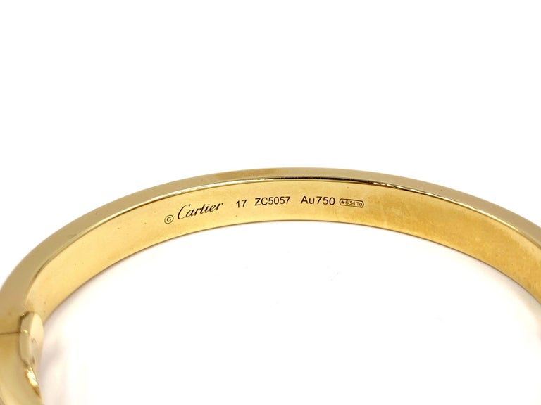 The iconic authentic Cartier LOVE bracelet made in 18 karat yellow gold with 204 brilliant-cut diamonds weighing 2.00 carats. Timeless design has a soft oval shape with gold nail heads. This bracelet is hinged and features a safety latch and push