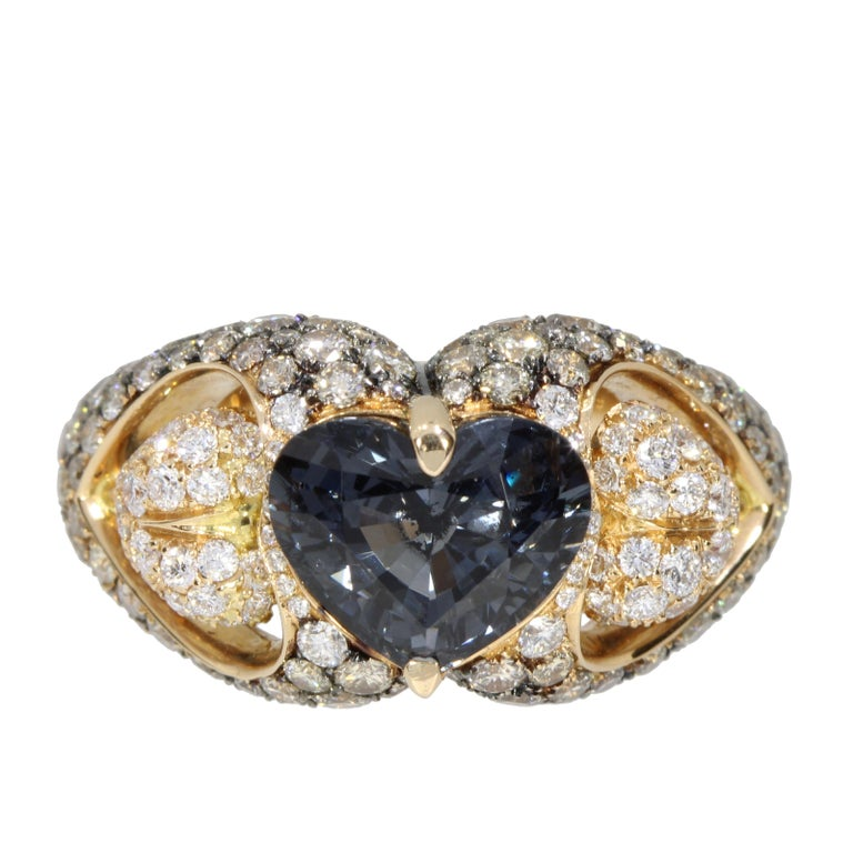 A captivating Blue Grey heart Spinel is the centre of two White diamonds pave hearts suspended ..... the hearts are surrounded by a glittering pave of black diamonds stones  This ring is an original new engagement ring but also the perfect present