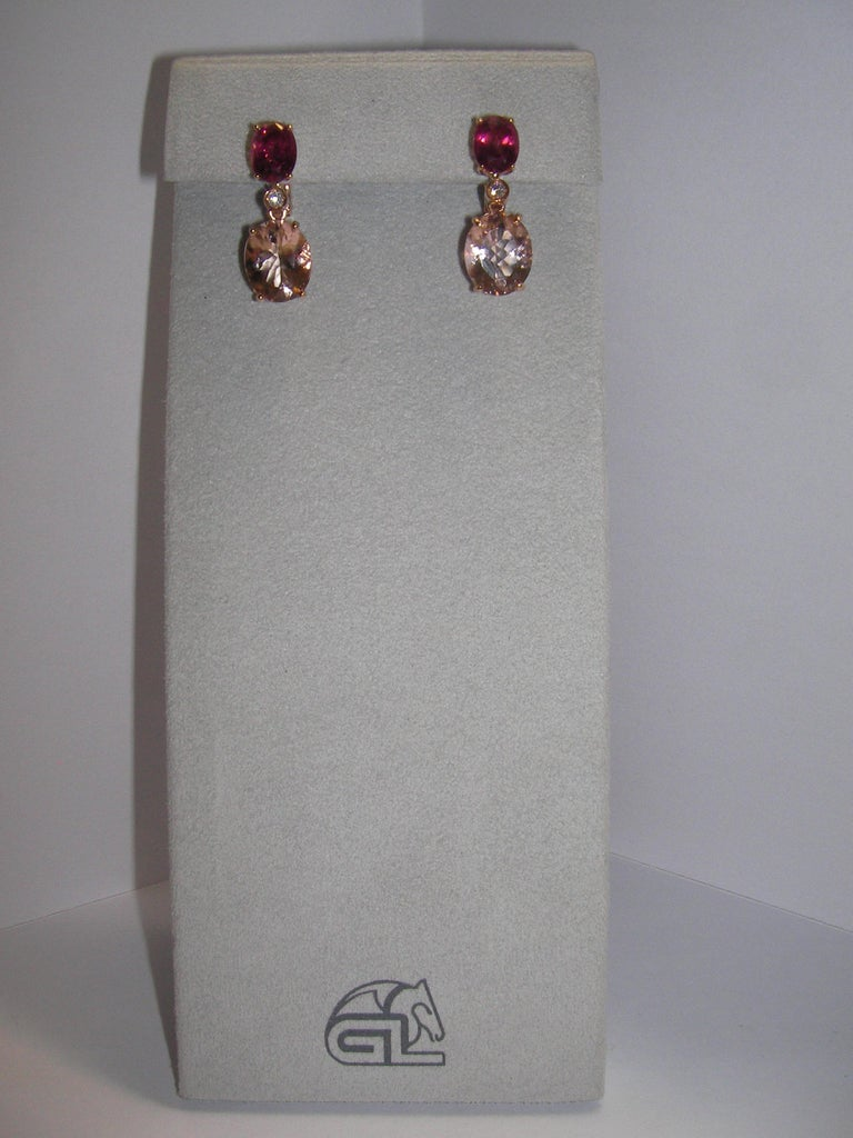 Classy set of earrings featuring a tourmaline base followed by a morganite stone. Both main stones are in oval cut and separated by a single diamond each.   2 Diamonds 0.07 Carat  2 Tourmaline 2.96 Carat  2 Morganite 6.28 Carat