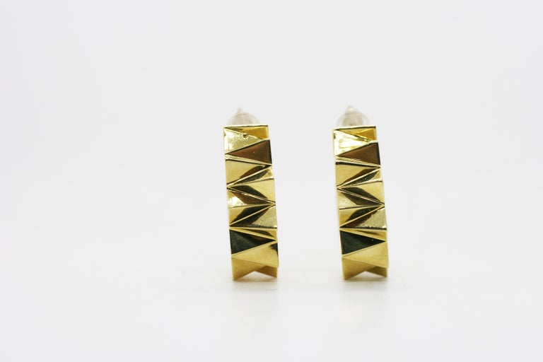 Small Folded Triangle Hoops feature two small circular hoops with repeating three dimensional triangles set in 18k Yellow Gold Includes push closure earring backings Sold as a Pair