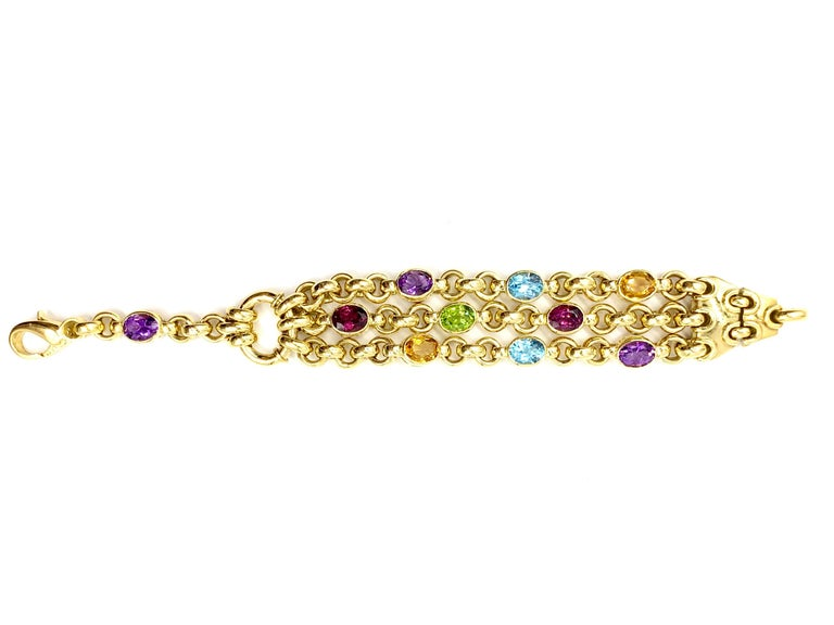 A very well made, high quality solid 18 karat yellow gold heavy link bracelet featuring three chains with scattered bezel set faceted oval semi precious gemstones. Gemstones are as follows: 3 amethysts, 2 Swiss blue topaz, 2 rhodolite garnets, 2