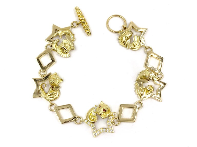 Created by expert jeweler Charles Turi. This vintage 18 karat yellow gold charm style bracelet with square and star links feature five different animals, including a panther adorned with ruby eyes. The panther rests upon a center star that is set