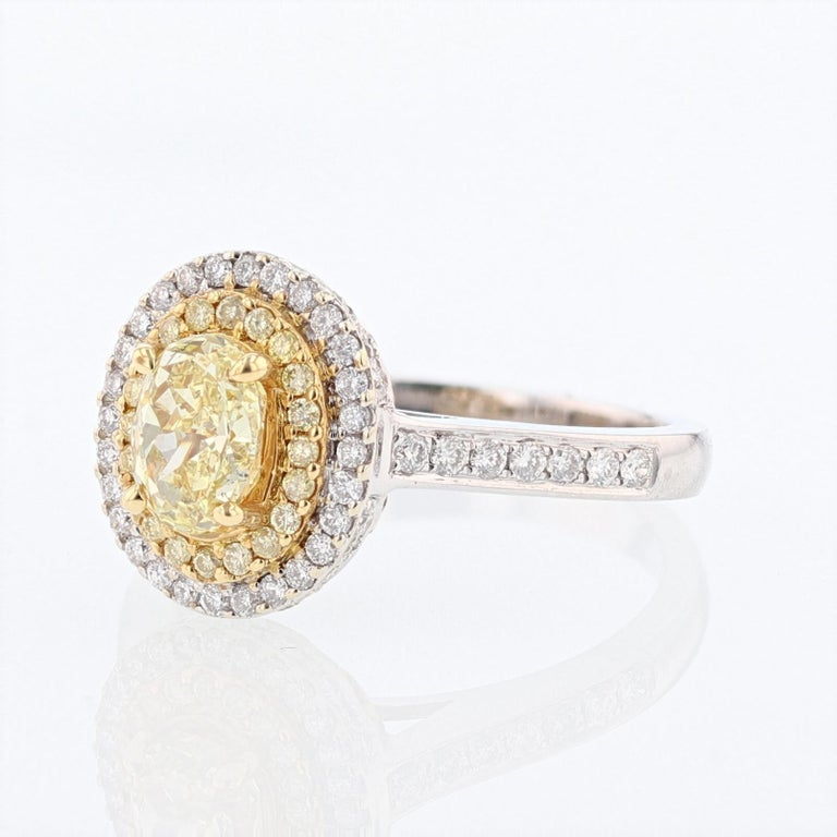 This ring is made in 18 karat white and yellow gold with featuring   an oval cut yellow diamond and a double halo with yellow and white diamonds. The center diamond is a 1.01 carat GIA certified  Yellow oval shape diamond with a color grade (FLY, or