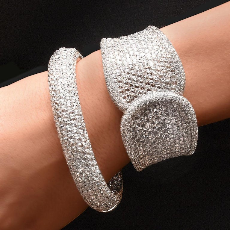 This beautiful 18 karat white gold cuff is handset with 619 Rose cut diamonds which total 19.42 carats, and is outlined with 8.36 carats of round brilliant diamonds. The oval shape cuff allows for a comfortable wear, and ensures that the unique