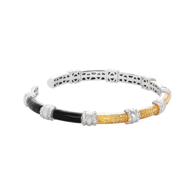 18 Karat White Gold Black Enamel Yellow Diamond Cuff Bracelet  This unique, light weight cuff bracelet set in 18 karat white gold studded with yellow diamonds and black enamel is perfect for a cocktail party or for evening wear.  Diamonds -