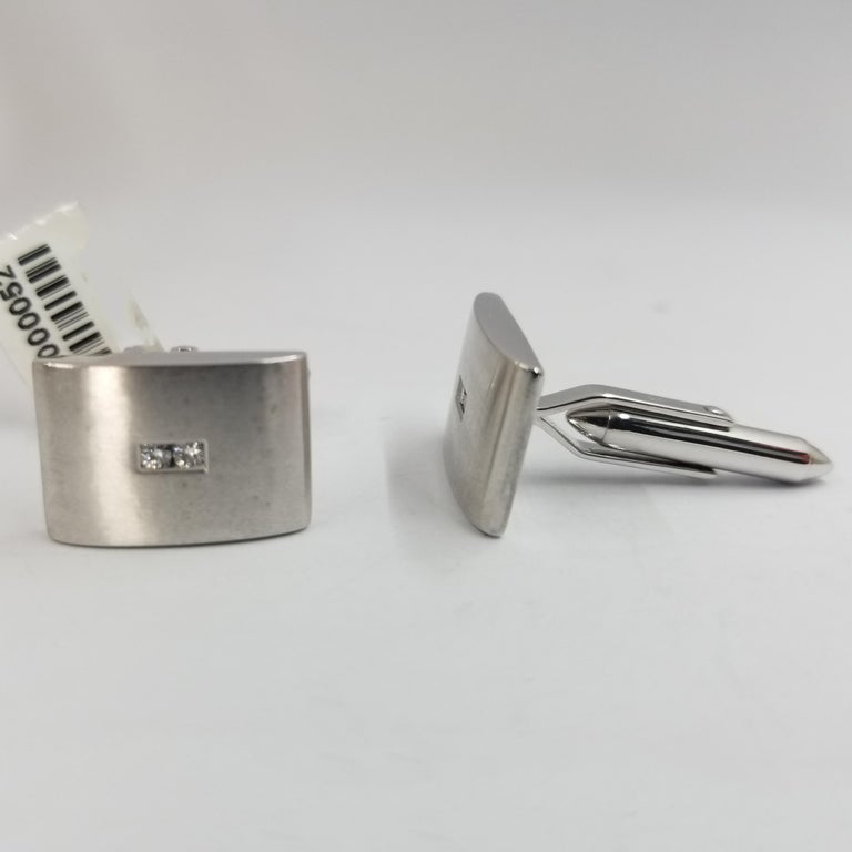 Set of 2 cufflinks crafted in 18 karat white gold (stamped). The fronts are brushed and curve outward with 2 channel set diamond each. Total weight is approximately 0.10 carat. The backs are a hinged torpedo style for easy dressing.