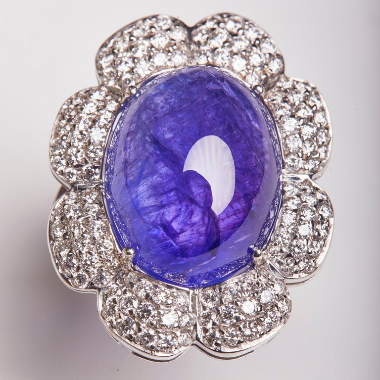 This 18 Karat White Gold Cocktail Ring full of Diamonds highlights a Tanzanite oval shaped center stone. This ring is a perfect compliment to our 18 Karat White Gold Diamond and Tanzanite Earrings and 18 Karat White Gold Diamond and Tanzanite Chain