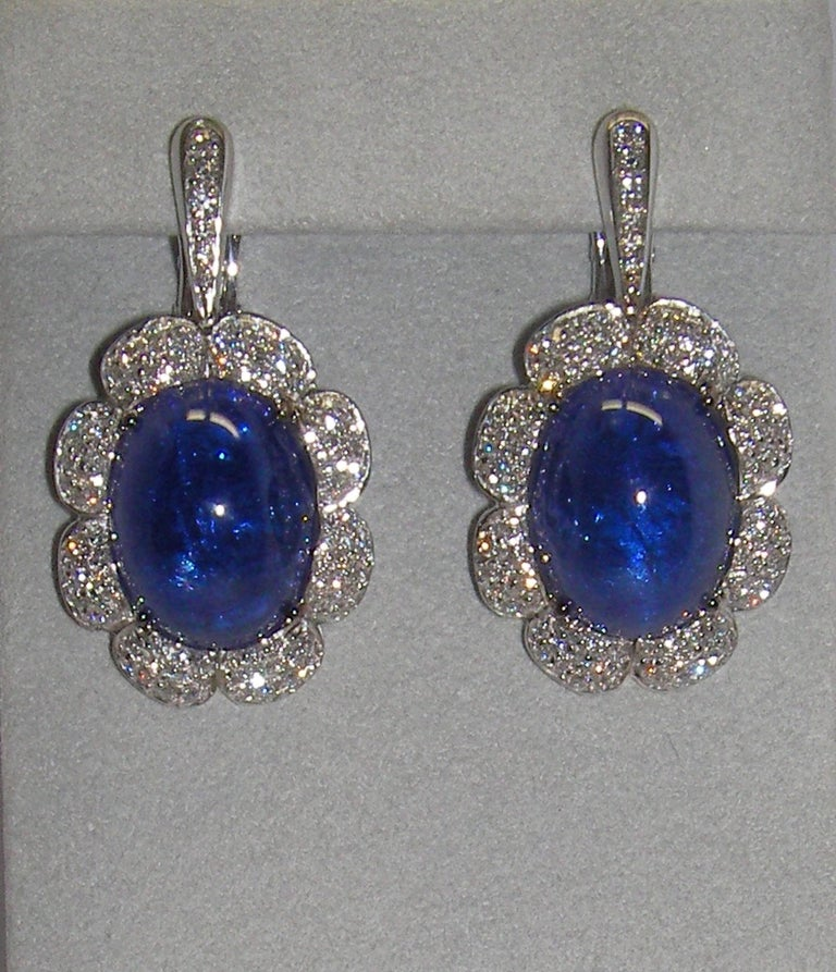 These stunning 18 Karat White Gold Drop Earrings full of Diamonds highlighting a Tanzanite oval shaped center stone on each earring. These earrings are a perfect compliment to our 18 Karat White Gold Diamond and Tanzanite Cocktail Ring and 18 Karat