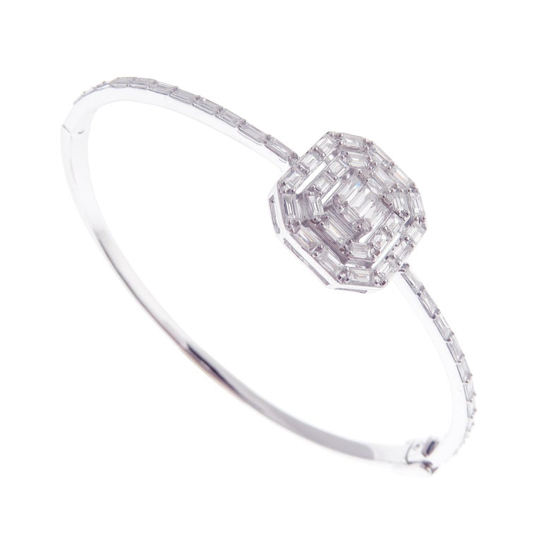 This delicate baguette square bangle is crafted in 18-karat white gold, weighing approximately 1.64 total carats of V-Quality white diamond. Side clasp closure.   Fits wrists up to 6.50