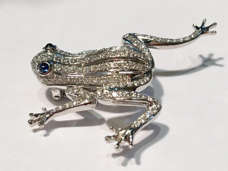 Contemporary 18 karat white gold brooch pin is a diamond frog with blue sapphire cabochon eyes and moving limbs.  Securely fastens with a double pin.  128 diamonds measure between 1 mm -  1.3 mm each and weigh approximately 1.5 carats total diamond