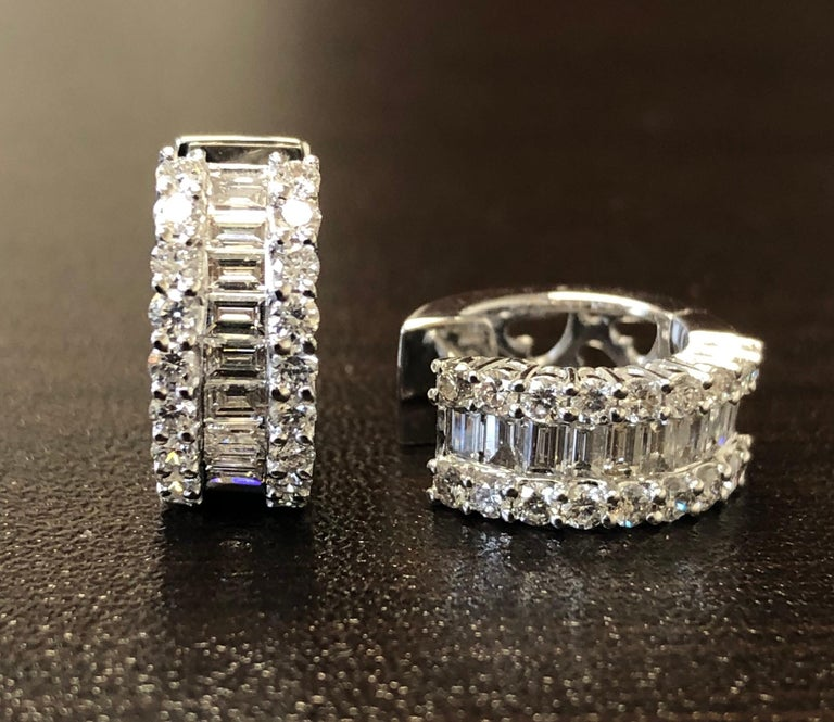Diamond Huggies set in 18K white gold. The diamonds are set halfway on the outside with baguette stones in the middle and 2 rows of round diamonds. The stones are F color, VS1-VS2 clarity. The total carat weight is 1.74, the carat weight of round