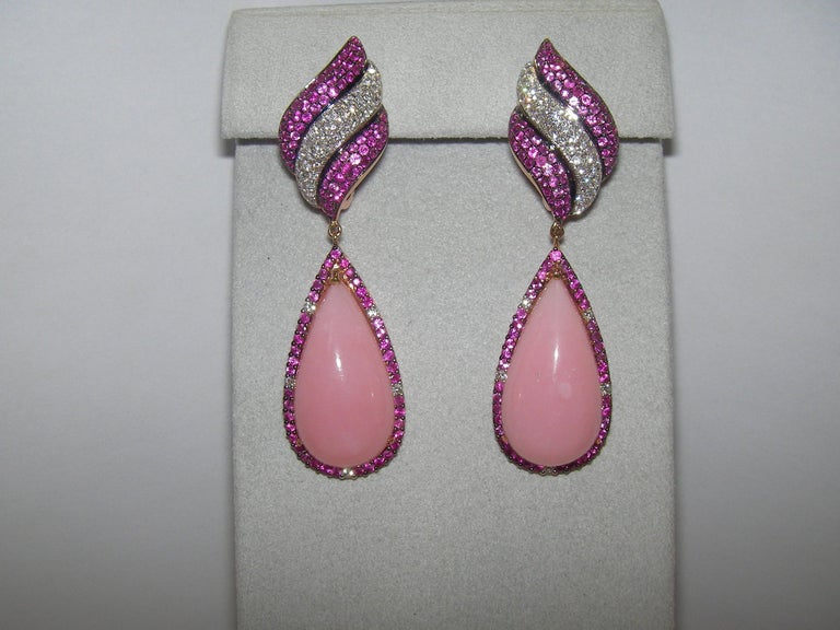 A marvelous pair of earrings, featuring a triad of diamond and pink sapphire pavé strands at the base, followed by a diamond and pink sapphire haloed pear-shape cabochon rose opal center stone of 14.5 carats each.  101 Diamonds 1.09 Carat  2 Rose