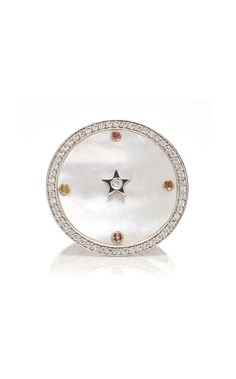 Inspired by the concept of time, Anna Maccieri Rossi's 'ORA Chevalier Ring' features a white mother of pearl dial with the hours of the day marked by multicolored sapphires with diamond star at center.