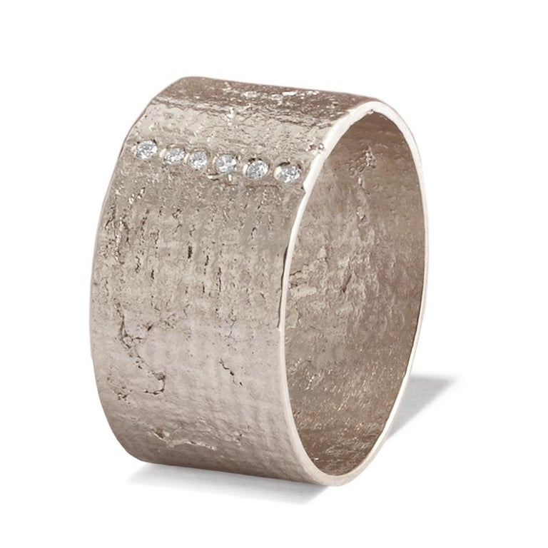 This classic textured wide cigar band ring crafted in solid 18-carat gold has a unique shimmering texture accented with six white diamonds. Diamonds are 1.2mm in diameter, H colour VS1 clarity with an approximate total carat weight of 0.05 carats.