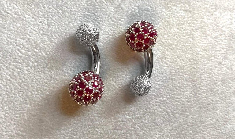 These elegant cufflinks are made entirely of 18k white gold. The large spherical front face is completely covered in rubies , while the toggle is shaped as a smaller sphere with a multi-faceted texture. A curved post with a polished, smooth surface