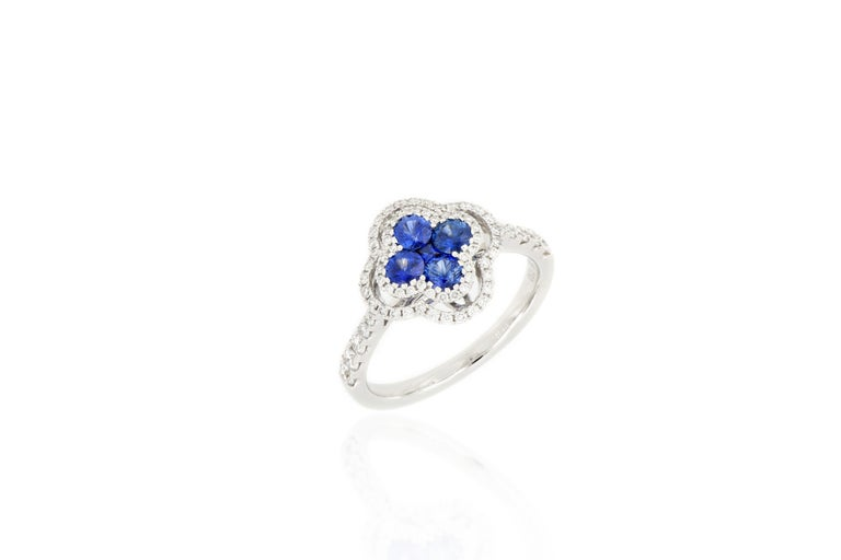 A fabulous sapphire and diamond ring. A cluster of natural sapphire arranged in the four-leaf clover pattern weighing 0.67cts, surrounded by brilliant-cut diamonds extending to the shoulders, total weighing 0.45cts, mounted in 18 karat white gold.