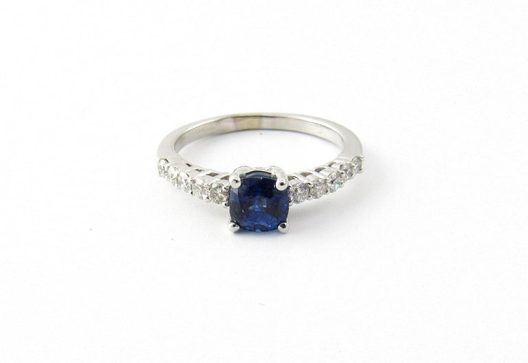 Vintage 18 Karat White Gold Sapphire and Diamond Ring Size 6.5-  This lovely ring features one round sapphire (5 mm) accented with ten round brilliant cut diamonds set in classic 18K white gold. Shank: 2 mm.  Approximate total diamond weight: .20
