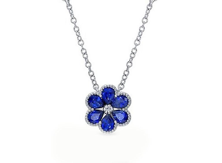 This enchanting floral necklace scintillates with 6 pear shaped sapphires totaling approximately 1.09 ctw with a round brilliant diamond in the center. The sapphire flower hangs on an 18kt white gold chain with two sparkling bezel set round