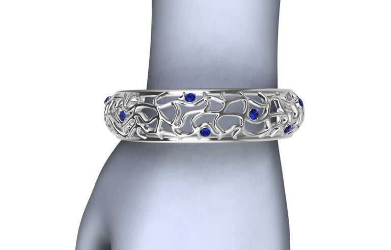 18 Karat White Gold Sapphire Synergistic Bangle,  AGTA, AA Ceylon blue diamond cut sapphires, 3.15  ct wt. What looks wild twisting, turning, and undulating, but held together with two rails. Accented throughout with sapphires popping ,adding more