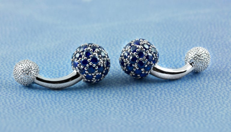 These elegant cufflinks are made entirely of 18k white gold. The large spherical front face is completely covered by sapphires , while the toggle is shaped as a smaller sphere with a multi-faceted texture.  A curved post with a polished, smooth