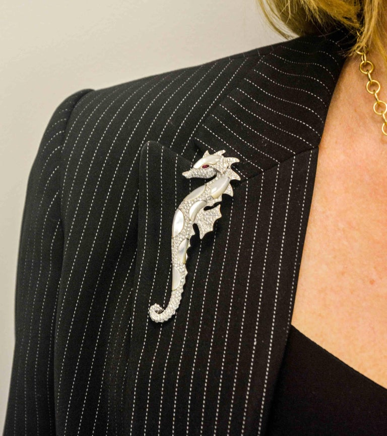 An exquisitely designed seahorse is crafted in 18 karat white gold. This dainty seahorse has ruby eyes (.02 ctw), abalone Mother-of-pearl and diamonds (2.50 carat total weight, G-H color, VS internal clarity). This brooch measures 3.5 inches and