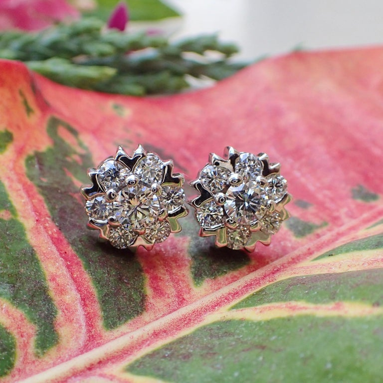 A pair of 18k white gold earrings contain two (2) Round Brilliant Cut diamonds that weigh a total of 0.55 carats that measure 4.25 x 4.25 mm with Clarity Grade VS with Color Grade G and twelve (12) Round Brilliant Cut diamonds that weigh a total of
