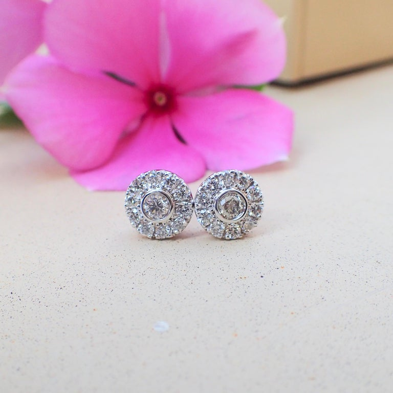 A pair of 18k white gold earrings are bezel set with two (2) Round Brilliant Cut diamonds measuring 2.5mm x 2.5mm that weigh a total of 0.12 carats with Cold Grade G and Clarity Grade VS and surrounding the center stones are twenty (20) prong set