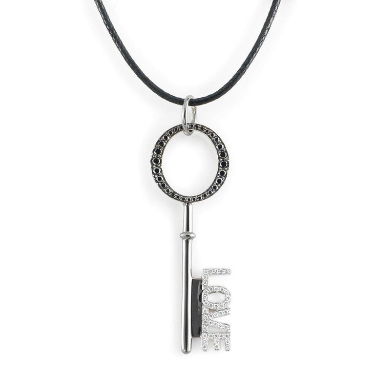 This LOVE Key Pendant with White and black diamonds is handcrafted in white gold, sterling silver, rhodium on a cotton cord.  Stones: White (F-G/VVS) and black diamonds: 0,43ct. Material: White Gold 18k, Sterling Silver 925, Black Rhodium  The