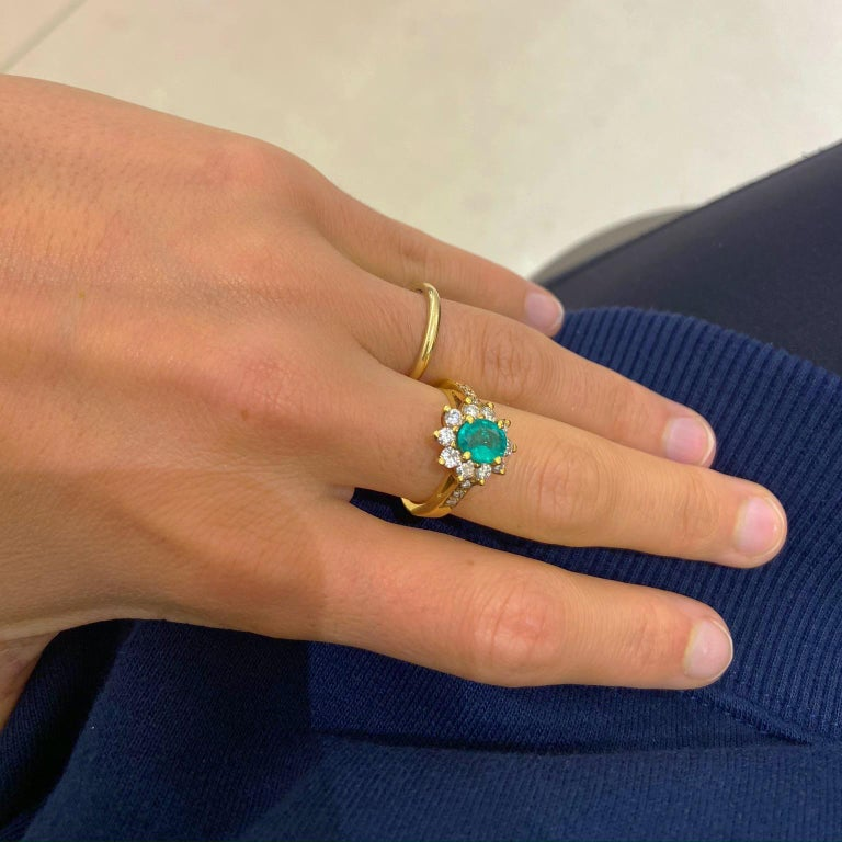 Set in 18 Karat Yellow Gold, is a beautiful .86Ct. Oval Emerald surrounded by .75Ct. of Round Diamonds set in a three prong setting.  10 Diamonds totaling .75 Carats.  Size: 6, Can be sized upon Request.  Available at Cellini Jewelers NYC