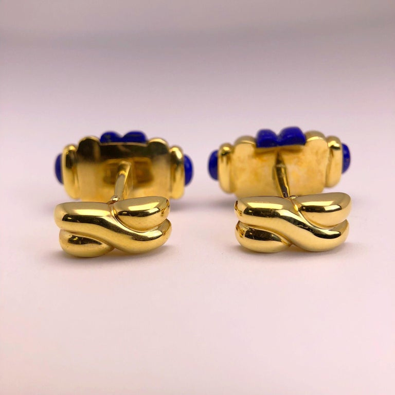 Created by George Gero, renowned worldwide for luxurious men's cuff-links, comes this classic  barrel shaped pair  which are set in 18 karat yellow gold  that alternates with carved Lapis Lazuli.   Collapsible backs are finished with a criss cross