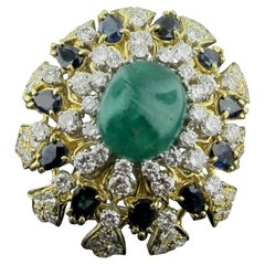 18 Karat Yellow Gold Brooch with Diamonds, Sapphires and a Cab Emerald Center