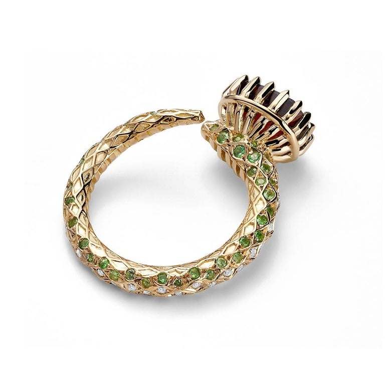 Designer cocktail ring in 18K yellow gold with a certified blood red spinel from Burma/Mogok, diamonds, and tsavorites. An alchemical motif of a serpent wearing a crown, with unique thorn like prongs. Entire body of the ring is intricately decorated