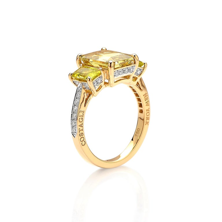 Emerald-cut Chrysoberyl ring flanked by yellow tourmaline side stones set in 18kt yellow gold with pave-set round, brilliant diamonds.  The clean lines of the cutting techniques and the exquisite pairing of the bright colored gemstones make this one